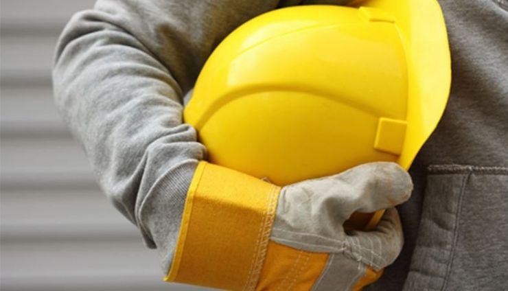 Man holding a yellow engineering hard hat